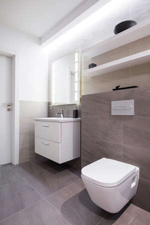 Grijze tegels in de badkamer in de moderne woning