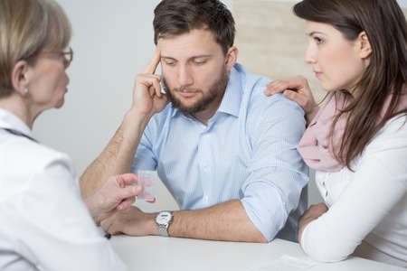 husband: Ill man and assisting wife ad doctors office Stock Photo