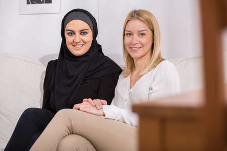 creed: Two happy women of different creed sitting together Stock Photo