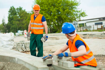 sidewalk talk: Young pavers working at a construction site Stock Photo