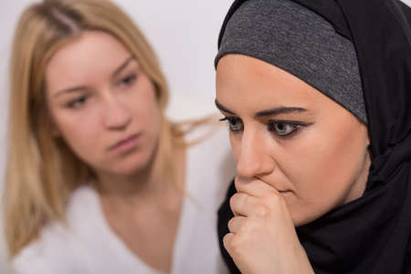 supportive: Terrified troubled muslim girl and supportive caucasian woman