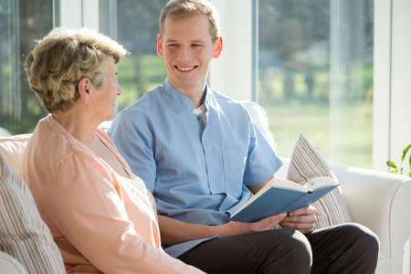 elderly: Young man reading book with elderly woman Stock Photo