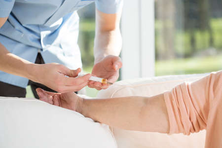 inyeccion: Hombre que hace la inyección a mujer mayor en su casa