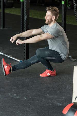 Man doet een been squat in de sportschool
