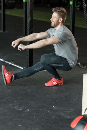 handguns: Man doing one leg squat at the gym