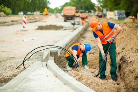 operarios trabajando: Trabajadores de la construcción renovación carretera en una gran ciudad