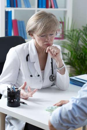 refusing: Portrait of elder doctor refusing a bribe