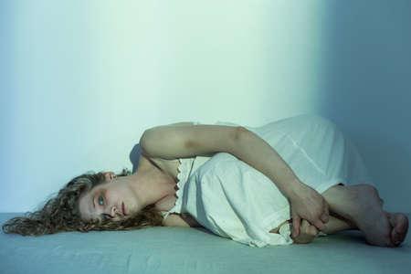 abuso sexual: Mujer molestado joven tumbado en el suelo