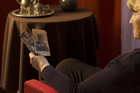 in loved: Grandmother watching photos of her loved ones from their youth