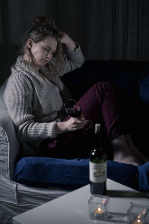 poverty: Young depressed drunk woman sitting in loneliness Stock Photo
