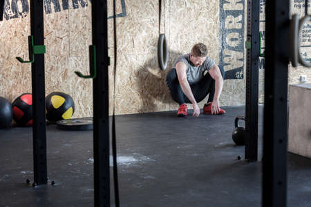 drained: Drained man after workout in cross fit center