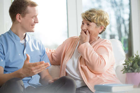 aging: Happy young man and elderly woman are laughing Stock Photo