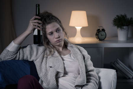 Young sad woman and lonely evening with bottle of wine