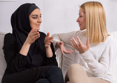 muslim: Two beautiful girls of different ethnicity talking