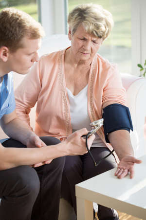 PULSE: Male nurse measures the pulse of an older woman