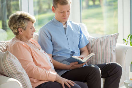health care worker: Male nurse reading book to old woman Stock Photo