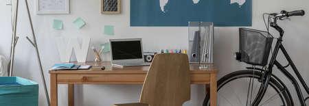 cosy: Panorama of bike standing beside wooden desk in cosy room