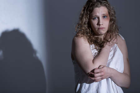 abuse young woman: Victim of sexual abuse on gray background