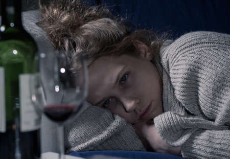 Young drunk sad woman lying on couch