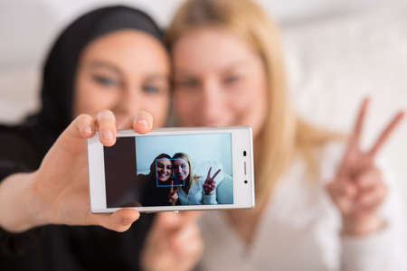 Muslim: Young muslim woman doing selfie with catholic friend Stock Photo