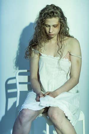 violencia sexual: Mujer víctima de la violencia sexual que se sienta en la silla Foto de archivo