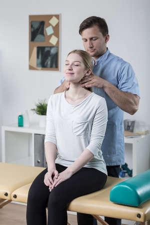 cervicales: Fisioterapeuta joven que hace la movilización de la columna cervical