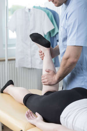 calf strain: Close-up of male physiotherapist doing functional massage
