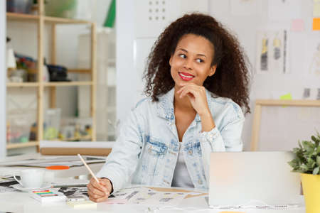 american content: Picture of ethnic content businesswoman with laptop at work Stock Photo