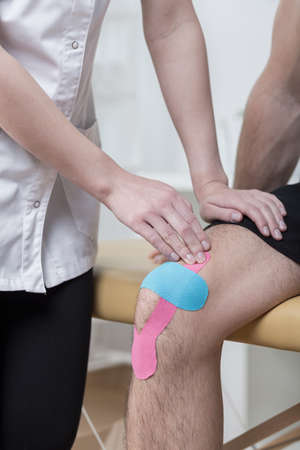 physical test: Close-up of kinesiology taping for painful knee