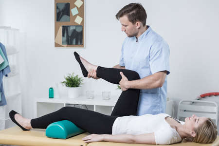 orthopedist: Male physiotherapist exercising with patient having knee pain