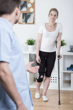 therapy room: Young woman using crutch after knee injury Stock Photo
