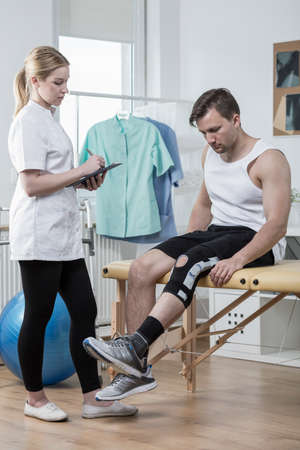 Man after knee ligament injury in physiotherapists office