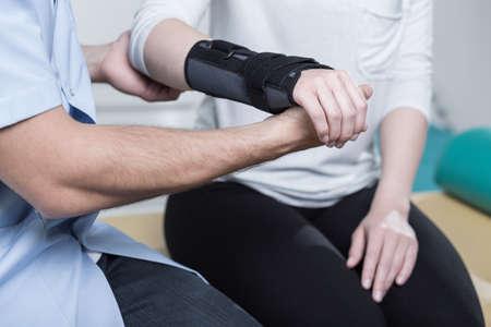 fisioterapia: Mujer que usa inmovilizador muñeca después de la lesión de la mano