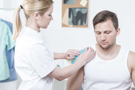medical therapy: Physiotherapist applying kinesiology tape for painful shoulder