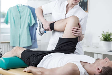 Female physiotherapist training leg of young man