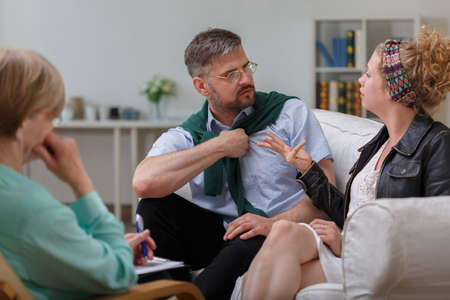couples therapy: Photo of husband arguing with wife during therapy with psychologist