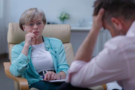 Foto van professionele vrouwelijke therapeut luisteren naar mannelijke patiënt