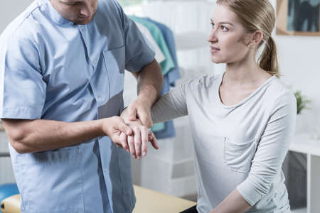 wrist pain: Woman with painful wrist at physiotherapists office