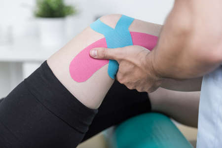physical training: Physiotherapist training with patient after knee injury
