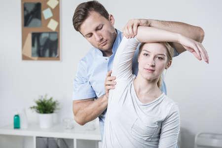 epaule douleur: Close-up de la formation de physioth�rapeute m�le avec le patient Banque d'images