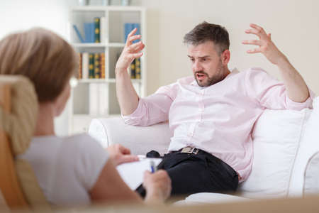 Image of upset male patient during psychotherapy session Stock Photo