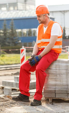Tired physical labourer in safety waistcoat and helmet Stock Photo