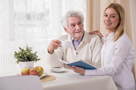 vecchiaia: Nonno e nipote bere caffè e leggere il libro