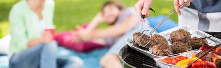 屋外ディナーの肉や野菜を焼く男のパノラマ 写真素材