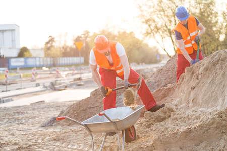 obrero: Constructores jovenes que trabajan en una obra en construcción
