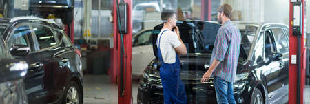 car workshop: Car mechanic is talking with his client