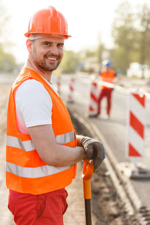 Vertical view of smiling adult construction worker