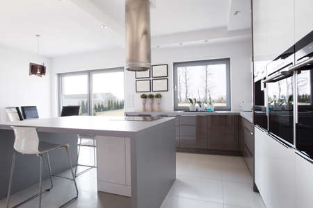 kitchen island: Modern and sunny kitchen with kitchen island in the middle