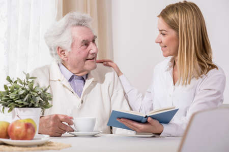 Care assistant and elder man reading book Stock Photo