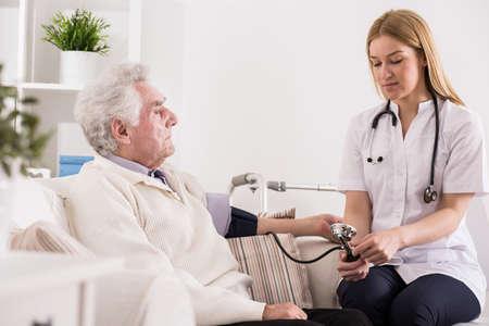 blood pressure cuff: Doctor measuring blood pressure of elder man